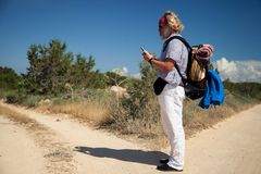Traveler consults his mobile phone at a crossroads in a rural landscape royalty free stock photography