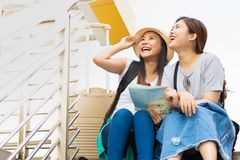 Traveler couple with backpacks sit on stair using generic local map together on sunny day stock photos