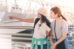 Traveler couple with backpacks using generic local map and pointing to right hand side on sunny day stock photography