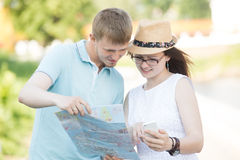 Traveler couple looking at map and phone for direction Stock Images