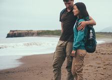 Traveler couple in love walking on beach near the sea. Traveler couple in love with backpacks walking on beach near the sea in summer. Man embracing a woman Stock Images