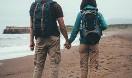 Traveler couple in love walking on sea beach Stock Images