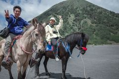 Traveler couple ride a horse at Mt. Bromo, east Java, Indonesia. Holding hand with fume of volcano background at Mt.Bromo Gunung Bromo Kingkong hill East Java royalty free stock image