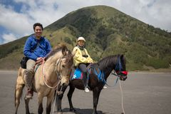 Traveler couple ride a horse at Mt. Bromo, east Java, Indonesia. Holding hand with fume of volcano background at Mt.Bromo Gunung Bromo Kingkong hill East Java royalty free stock images