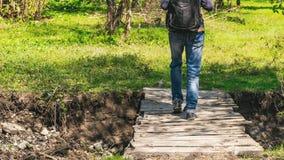 Traveler crosses forest river through old wooden bridge. Traveler with backpack crosses forest river through old wooden bridge Stock Photography