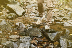 Traveler crossing the stream Stock Photos