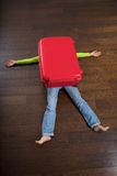 Traveler crushed by red suitcase Royalty Free Stock Photography