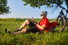 Traveler cyclist have a rest under oak tree with his bike behind him on summer afternoon. Stock Photography