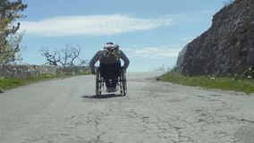 Traveler Disabled Man On Mountain Road. Slow motion shot of a traveler disabled man with a backpack in wheelchair walking on mountain road stock footage