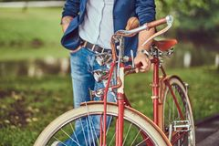 Traveler dressed in casual clothes with a backpack, relaxing in a city park after riding on a retro bicycle. A traveler dressed in casual clothes with a royalty free stock photos