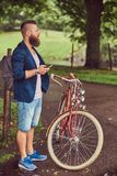 Traveler dressed in casual clothes with a backpack, using a smartphone, relaxing in a city park after riding on a retro. A traveler dressed in casual clothes stock photos