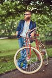 Traveler dressed in casual clothes and sunglasses with a backpack, relaxing in a city park after riding on a retro. A traveler dressed in casual clothes and stock photography