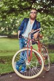 Traveler dressed in casual clothes and sunglasses with a backpack, relaxing in a city park after riding on a retro. A traveler dressed in casual clothes and royalty free stock images