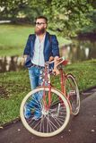 Traveler dressed in casual clothes and sunglasses with a backpack, relaxing in a city park after riding on a retro. A traveler dressed in casual clothes and stock photos