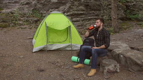 Traveler drinks water sitting next to the tent. stock footage