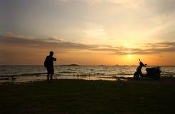Traveler enjoying sunset with his bike Stock Image