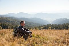 A man with equipment in search of a route in the mountains. A traveler with equipment sits in a dry grass on a mountain ridge stock photography