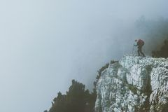 Traveler on foggy cliff mountains Stock Photo