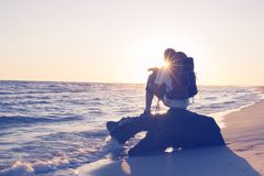 Traveler, with funny small dog. Sits on a snag in the surf, in the rays of setting sun and admires the sea. Amazing adventure on the seashore. Back view, back Stock Photography
