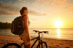 Traveler girl with backpack enjoying view of beautiful sunset. Royalty Free Stock Images