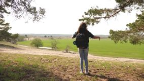 Traveler girl with a backpack on her shoulders and a dog straightens her arms to the side enjoying freedom. Traveler girl with a backpack on her shoulders and a stock footage