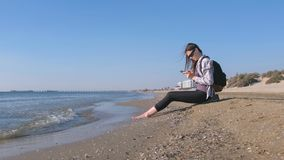 Traveler girl with a backpack sitting on a sandy sea beach and typing a message on mobile phone. stock photos