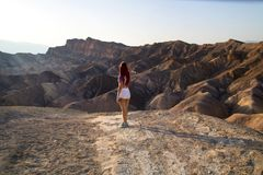 Traveler girl with fit body is standing in white short shorts in front of dry hot lifeless desert landscape, Zabriskie Point USA. Woman standing in the desert royalty free stock photography