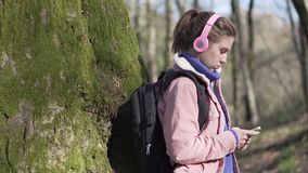 Traveler girl in the forest with mobile phone. Caucasian girl in the forest with a mobile phone. Young tourist on vacation in the forest stock video footage