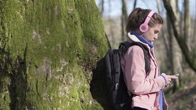 Traveler girl in the forest with mobile phone. Young tourist on vacation in forest stock footage
