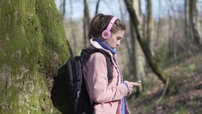 Traveler girl in the forest with mobile phone. Young tourist on vacation in forest stock video footage