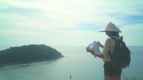 Traveler Girl Holding Map With Travel Destinations. Young woman tourist with backpack and a map in her hands looking in trip holiday in island stock video footage