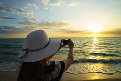 Traveler girl photographing sun at sunset on the beach Stock Photography