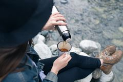 Traveler girl pouring tea from thermos cup, outdoors. Young woman drinking tea at cup. Theme travel. Woman pouring a hot. Drink in mug from thermos. Girl Stock Photography