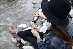 Traveler girl pouring tea from thermos cup, outdoors. Young woman drinking tea at cup. Theme travel. Woman pouring a hot. Drink in mug from thermos. Girl Stock Photo