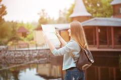 Traveler girl searching right direction on map, orange sunset light, traveling along Europe Stock Photo