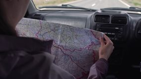 Traveler girl sitting in the driving car looking map and find the way