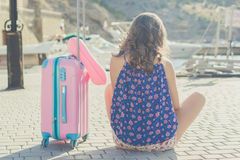 Traveler girl is sitting with pink suitcase Stock Photo