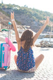 Traveler girl is sitting with pink suitcase Stock Images
