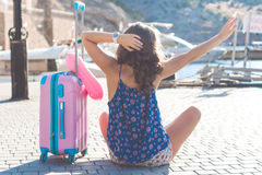 Traveler girl is sitting with pink suitcase Stock Image