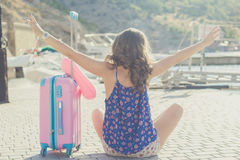 Traveler girl is sitting with pink suitcase Royalty Free Stock Image