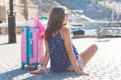 Traveler girl is sitting with pink suitcase Royalty Free Stock Photography