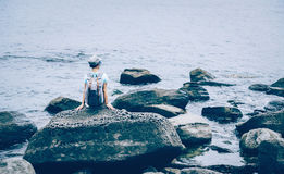 Traveler girl sitting on stone in the sea Stock Image