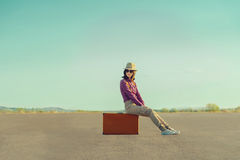 Traveler girl sitting on suitcase on road in summer. Smiling traveler girl in hat and sunglasses sitting on suitcase on road in summer Royalty Free Stock Photos