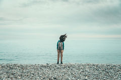 Traveler girl standing on coast in windy weather Royalty Free Stock Photography
