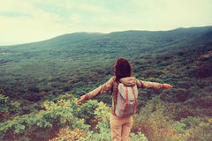 Traveler girl standing with raised arms on mountain Royalty Free Stock Photos