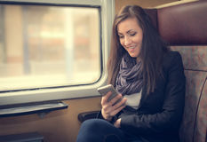 Traveler girl use the phone on train Royalty Free Stock Photo