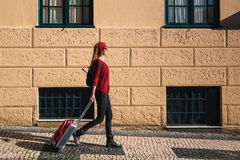 Traveler girl walking in city with red suitcase. Europe. Stock Images