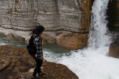 Traveler girl walking in waterfall canyon. Travel adventure and hiking activity, active and healthy lifestyle Royalty Free Stock Photo