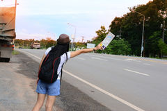 A  traveler girl in white shirt hold a map  and waving her hand Stock Photo