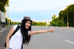 A traveler girl in white shirt waving her hand for some help f. Rom the car on the road royalty free stock photo